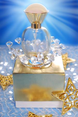 christmas perfume: bottle of perfume standing on golden box in christmas scenery