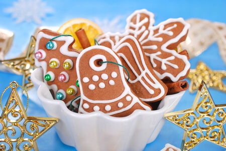 homemade christmas gingerbread cookies decorated with icing and spices in white bowl on blue background photo