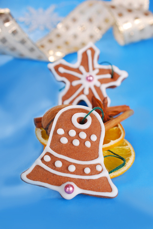 homemade christmas gingerbread cookies decorated with icing and spices on blue background photo