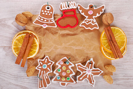 christmas frame with homemade gingerbread cookies,spices, nuts on old paper and wooden background Stock Photo - 24431674