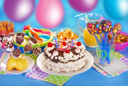 pops: chocolate torte with candles and homemade sweets for children birthday party