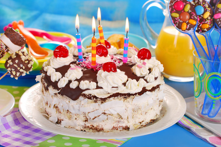 chocolate torte with candles and homemade sweets for children birthday party