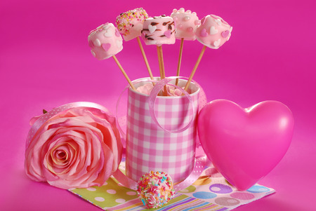 candy stick: pink marshmallow pops with heart shape and pearl sprinkles in cup for valentine