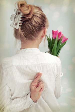 young girl holding bunch of tulips in one hand and second hiding on the back with crossed fingers  vintage style  photo
