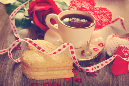 cup of coffee and heart shaped cookies with sugar for valentine on wooden table in vintage style photo