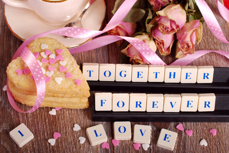 declaration: love words made of letters ,dried roses  and heart shaped cookies with sprinkles  for valentine on wooden table