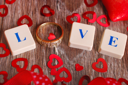 love word made of alphabet tiles letters and golden ring  for valentine on wooden table photo
