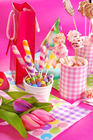 kids birthday party: colorful birthday party table with flowers,gift and homemade sweets for kids