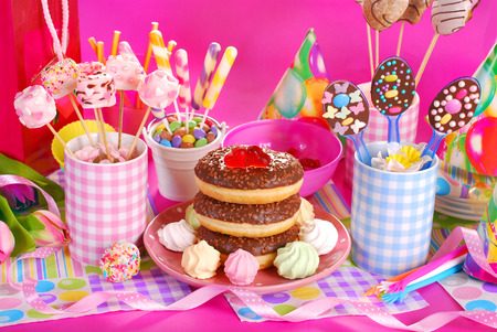 colorful birthday party table with flowers,gift and homemade sweets for kids