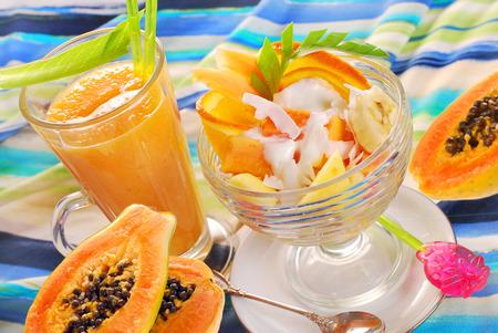 mix fruit: glass of fresh fruits smoothie and salad with papaya,banana,orange,pineapple,apple and coconut flakes poured yogurt  Stock Photo