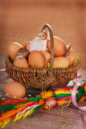 pasen schaap: rural braided basket with fresh eggs and little sheep figurine on wooden table for easter