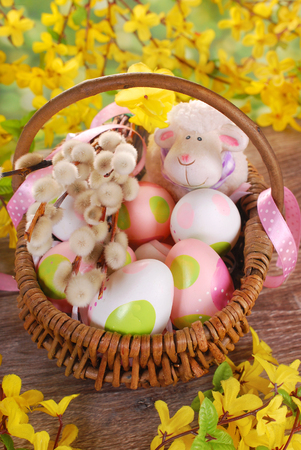 rural braided basket with fresh eggs and funny sheep figurine on wooden table for easter photo