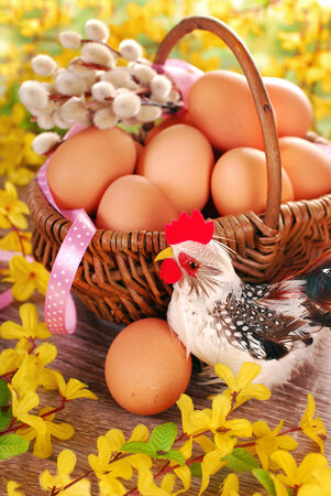 willows: rural braided basket with fresh eggs and chicken figurine on wooden table for easter Stock Photo