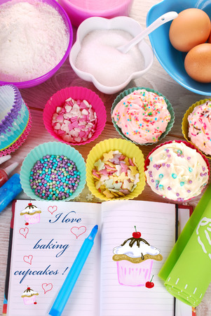 bowls of ingredients needed for baking colorful cupcakes and notebook with text and drawing   photo