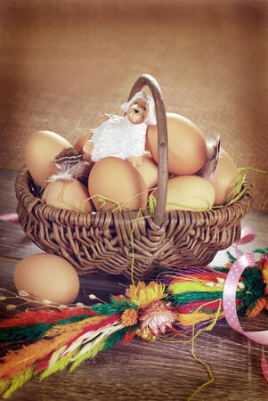 rural braided basket with fresh eggs and little sheep figurine on wooden table for easter in vintage style  photo
