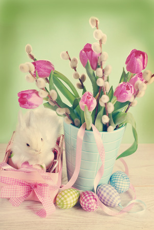 vintage easter decoration with pink basket ,eggs and fresh tulips in vase on green background photo