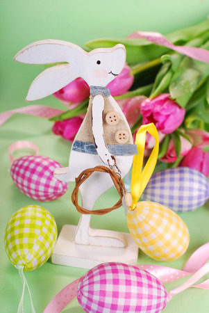 easter decoration with standing wooden bunny and fresh tulips on green background photo