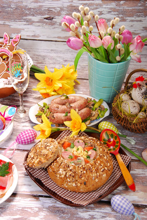 traditional polish dishes for easter dinner -white borscht  zurek  with sausage,egg and mushrooms in bread as bowl on old wooden table photo