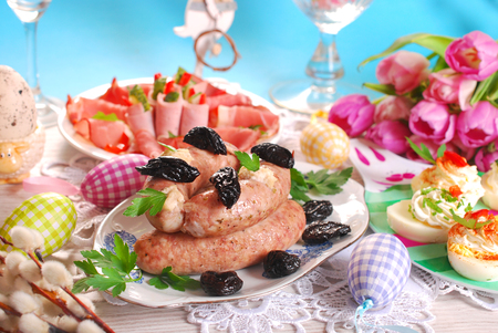 easter table with traditional dishes - white sausage,stuffed eggs and ham slices photo