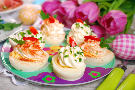 egg halves stuffed with cheese and mayonnaise decorated with red pepper and chives for easter photo