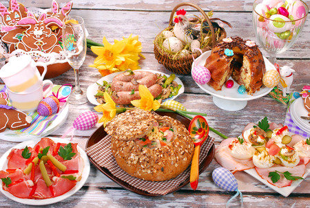 easter basket: traditional polish dishes for easter dinner -white borscht  zurek  with sausage,egg and mushrooms in bread as bowl on old wooden table