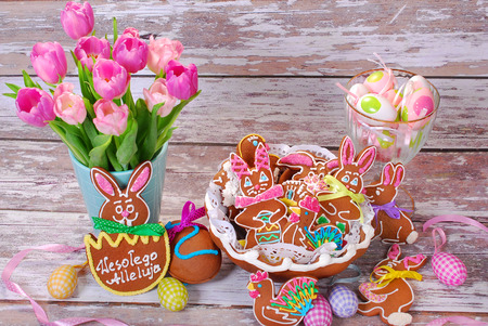 easter table decoration with handmade gingerbread cookies in basket on old wooden  photo