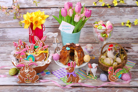 easter table decoration with handmade gingerbread cookies in basket and ring cake on old wooden  photo