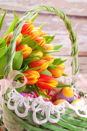easter basket with colorful eggs and bunch of fresh yellow-red tulips photo