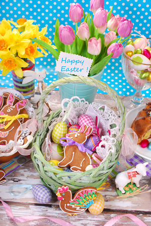 easter decoration with wicker basket,eggs,gingerbread cookies and fresh tulips and daffodils on blue dotted background photo