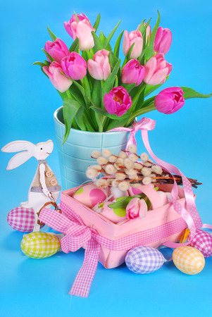 easter decoration with standing wooden bunny figurine, pink basket ,fresh tulips in vase and eggs in pastel colors photo