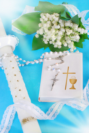 white prayer book,rosary,candle and lily of the valley bouquet as symbols of the first holy communion photo