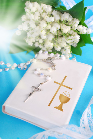 white prayer book,rosary and lily of the valley bouquet as symbols of the first holy communion