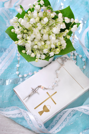 bunch of fresh lily of the valley flowers and white prayer book with rosary on blue background for the first holy communion