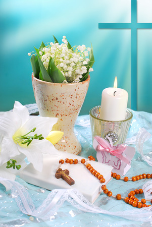 the first holy communion still life with prayer book,rosary,candle and flowers on blue background photo