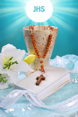 primera comunion: la primera comunión sigue la vida con cáliz, rosario de madera, libro de oraciones y el lirio sobre fondo azul Foto de archivo