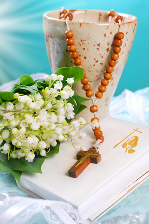 the first holy communion still life with chalice,wooden rosary, prayer book and lily of the valley on blue background Stock Photo