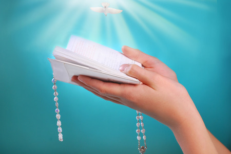 hands of a girl going to the first holy communion holding prayer book with rosary on blue background photo