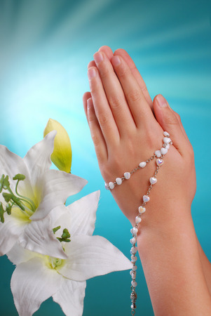 hands of a girl going to the first holy communion prying with rosary on blue background