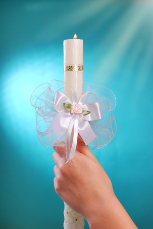 hands of a girl going to the first holy communion holding white candle with flame on blue background photo
