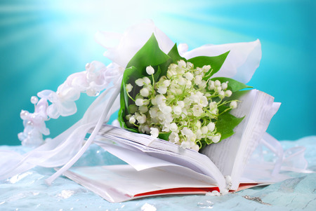 the first holy communion still life with opened prayer book and bunch of lily of the valley on blue Zdjęcie Seryjne - 28467448