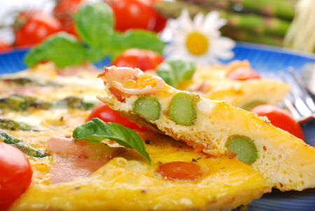 frittata with green asparagus,prosciutto ham and grilled cherry tomato on blue plate photo