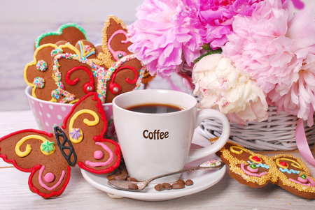 cup of coffee and butterfly shaped gingerbread cookies for summer party  photo