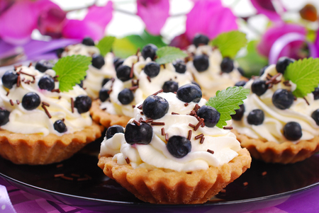delicious blueberry tartlets with whipped cream and chocolate sprinkles photo