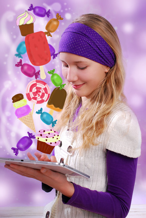 crave: beautiful young girl using digital tablet PC and choosing something sweet to eat  Stock Photo