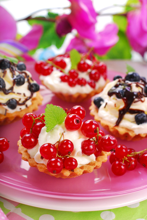 mini tartlets with whipped cream ,fresh red currant and blueberry poured chocolate sauce photo