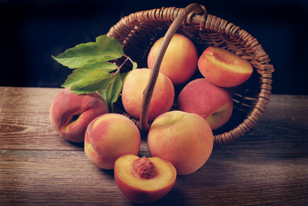 falling out: delicious fresh peaches falling out of a wicker basket on wooden