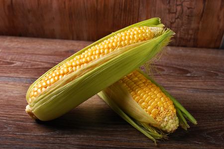 fresh raw sweet corn cobs on wooden background  版權商用圖片
