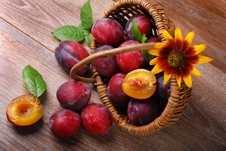 falling out: fresh  plums falling out of a wicker basket on wooden background