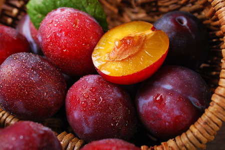 falling out: fresh wet plums falling out of a wicker basket on wooden background