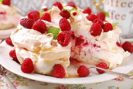 Pastel de merengue pavlova con nata, caramelo y frambuesas frescas Foto de archivo - 31518130